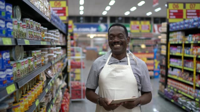 portrait of supermarket employee using tablet - grocer stock videos & royalty-free footage