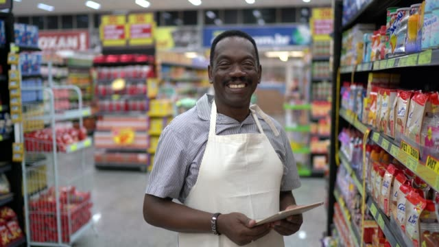 vídeos y material grabado en eventos de stock de retrato de empleado del supermercado usando tablet - tendero