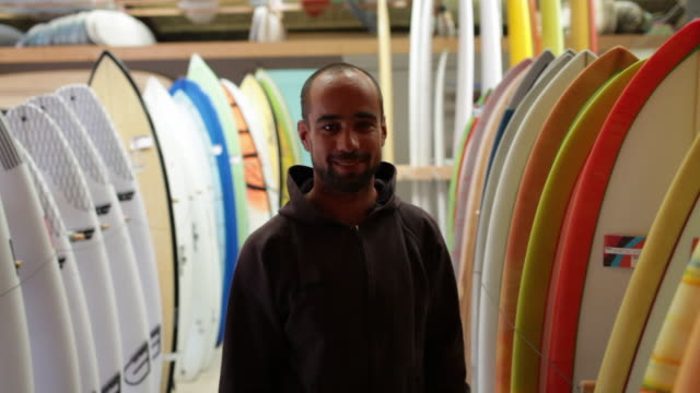 Portrait of surfboard shaper standing in shop next to surfboards