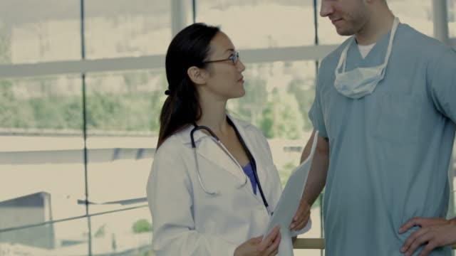 vidéos et rushes de ms tu portrait of surgeon and female doctor in hospital hallway / vancouver, british columbia, canada - masque de chirurgien