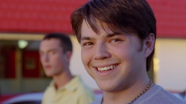 portrait of teenage boy smiling at camera with friend hanging out in background - one teenage boy only stock videos & royalty-free footage
