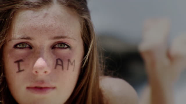 ms portrait of teenage girl outdoors with 'i am' written on face, laguna beach, california, usa - kelly mason videos stock-videos und b-roll-filmmaterial