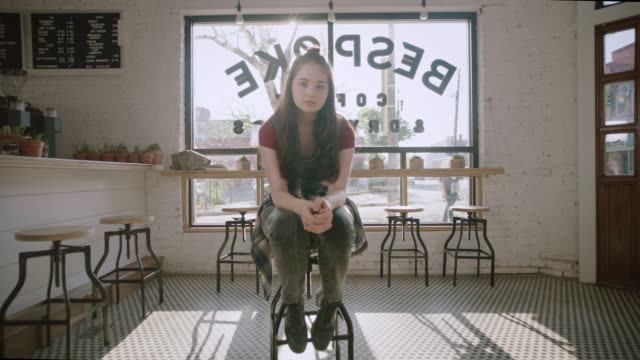 stockvideo's en b-roll-footage met ws slo mo. portrait of teenage girl sitting on bar stool in hip local coffee shop. - tekst