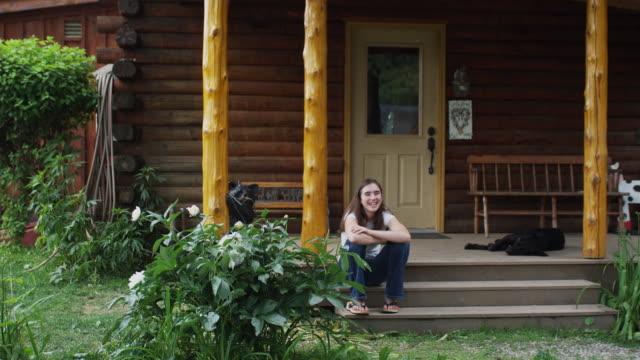 ms portrait of teenage girl sitting on steps outside log cabin, sunderland, vermont, usa - one teenage girl only点の映像素材/bロール