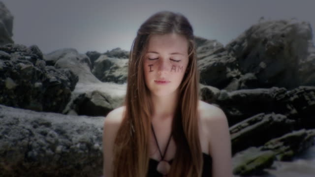 ms portrait of teenage girl standing by rocks with 'i am' written on face and 'present' on arm, laguna beach, california, usa - kelly mason videos stock-videos und b-roll-filmmaterial