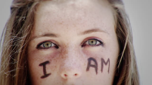 ecu portrait of teenage girl with 'i am' written on face, laguna beach, california, usa - kelly mason videos stock-videos und b-roll-filmmaterial