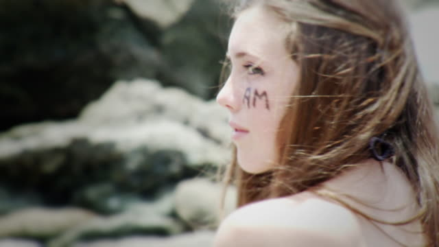 cu portrait of teenage girl with 'i am' written on face sitting by rocks, laguna beach, california, usa - kelly mason videos stock-videos und b-roll-filmmaterial