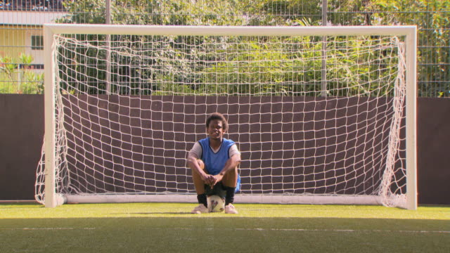 WS Portrait of teenage (16-17) soccer player sitting in front of goal post, London, UK