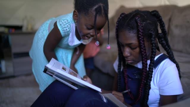 vidéos et rushes de verticale de fille d'adolescent faisant des devoirs à la maison - enfant d'âge scolaire