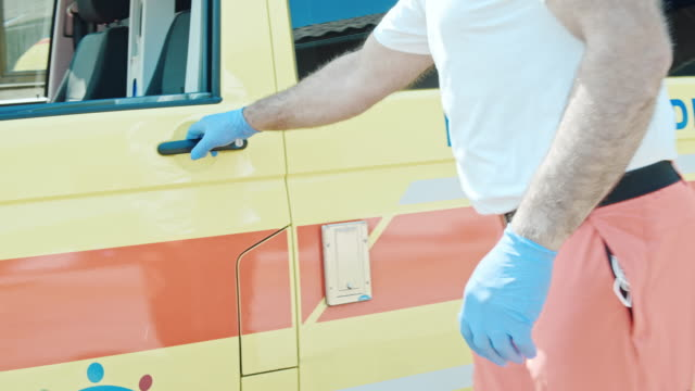slo mo portrait of the ambulance driver getting into the vehicle - soccorritore video stock e b–roll