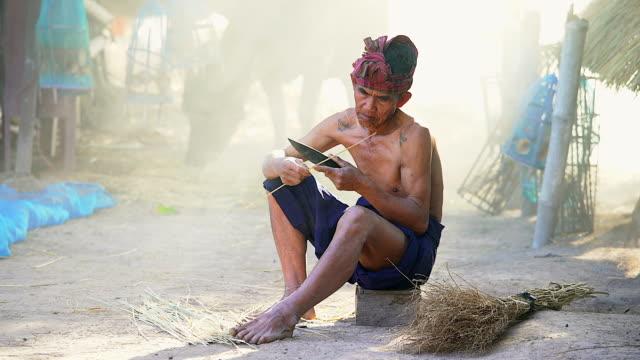 vidéos et rushes de portrait du vieil homme asiatique fait son travail et en regardant la caméra. - indonésie