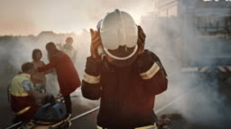 Portrait of the Brave Firefighter Taking Off His Helmet. In the Background Courageous Heroes Paramedics and Firemen Rescue Team Fight Fire, Smoke and Save People's Lives