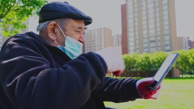 stockvideo's en b-roll-footage met portret van de senior 90-jarige man het dragen van een beschermend masker en handschoenen als gevolg van de covid-19 pandemie, met behulp van een smartphone voor video-gesprek met zijn familie. - hoofddeksel