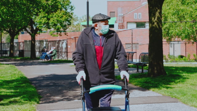 portrait of the senior 90-years-old man wearing protective mask and gloves because of the covid-19 pandemic walking outdoor in a park using a walker and maintaining social distancing. - town square stock videos & royalty-free footage