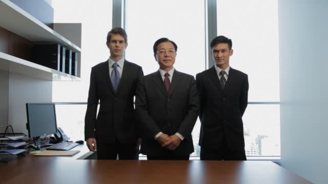 ms portrait of three businessman standing behind desk / china - arbeitskollege stock-videos und b-roll-filmmaterial