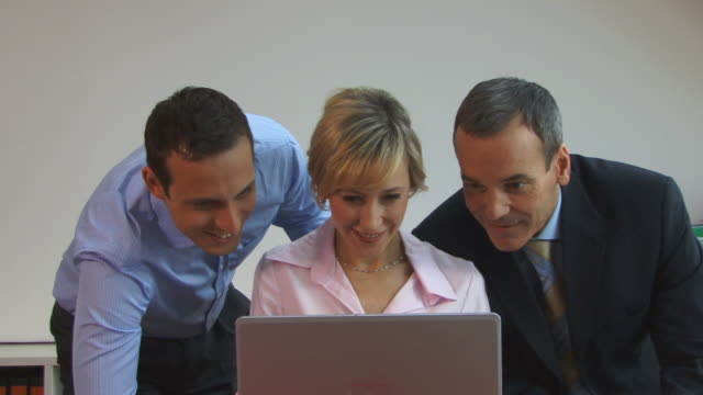 cu, portrait of three businesspeople looking at laptop in office, berlin, germany - central europe stock videos and b-roll footage