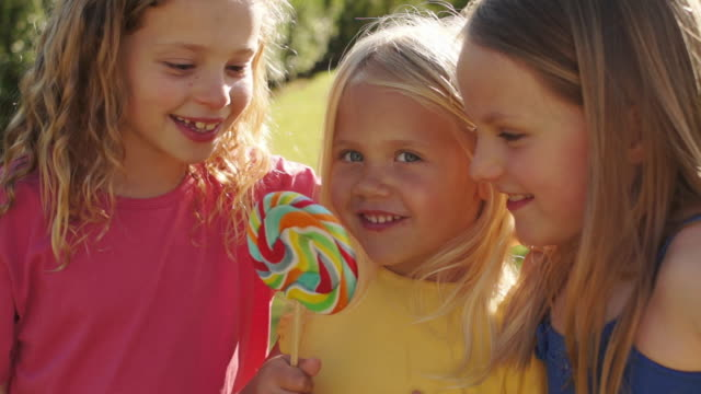 portrait of three children licking lollypop in park. - lollipop stock videos and b-roll footage