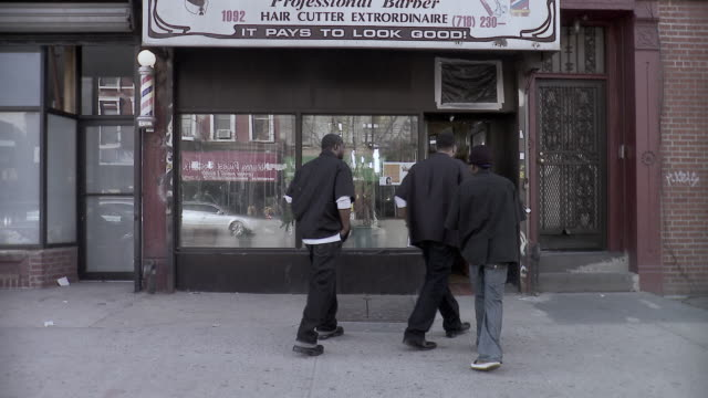 ms portrait of three men standing in front of barbershop then walking inside it, brooklyn, new york city, new york state, usa - 少人数点の映像素材/bロール