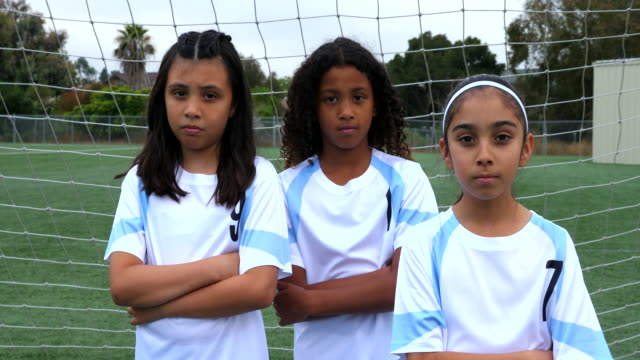 ms portrait of three serious young female soccer players standing in front of goal - attitude stock videos & royalty-free footage