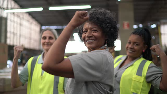 portrait of three woman working in a warehouse striking a strong woman pose - working seniors stock videos & royalty-free footage