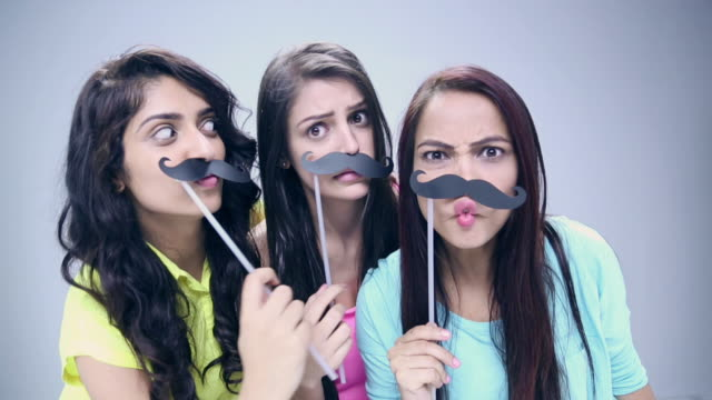Portrait of three young women applying moustache