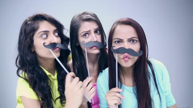 vídeos de stock, filmes e b-roll de portrait of three young women applying moustache - bigode