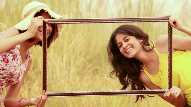 vídeos y material grabado en eventos de stock de portrait of three young women looking through from a frame, delhi, india - marco