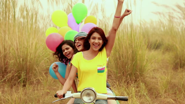 portrait of three young women sitting on a scooter in the forest, delhi, india - schiebermütze stock-videos und b-roll-filmmaterial