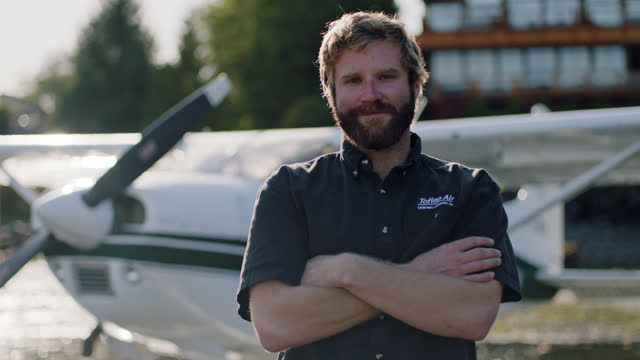 portrait of tofino floatplane pilot crossing arms and smiling at camera. - outdoor pursuit stock videos & royalty-free footage