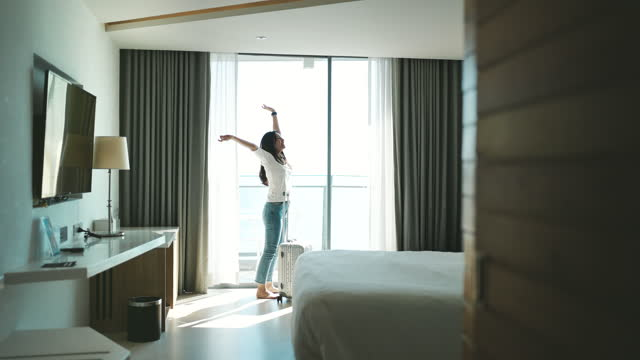 portrait of tourist woman standing nearly window, looking to beautiful view with her luggage in hotel bedroom after check-in - arrival stock videos & royalty-free footage