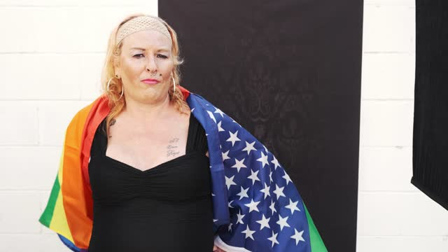 portrait of transgender woman with pride usa flag against black backdrop - pink hair stock videos & royalty-free footage