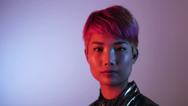 portrait of trendy asian gender fluid person looking to camera with neon lights - neon stock videos & royalty-free footage