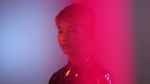 Portrait of trendy Asian gender fluid person looking to camera with neon lights