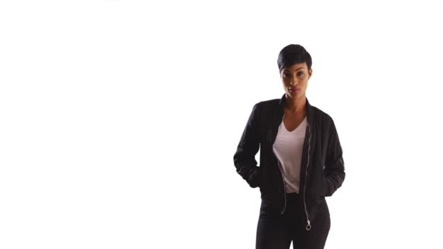 portrait of trendy black woman posing with hands in jacket pockets in studio - hands in pockets stock videos & royalty-free footage