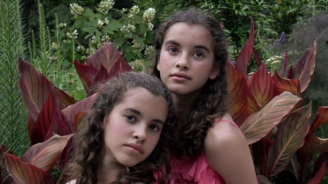 CU Portrait of twin sisters (12-13) in garden, Chapel Hill, North Carolina, USA