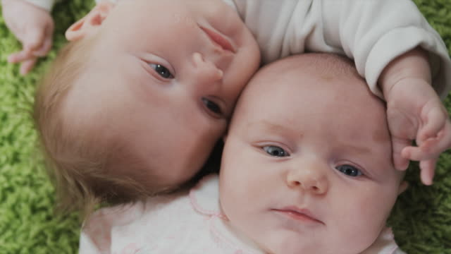 cu ha portrait of two babies (2-5 months) lying on green carpet, brussels, belgium - 2 5 months stock videos & royalty-free footage