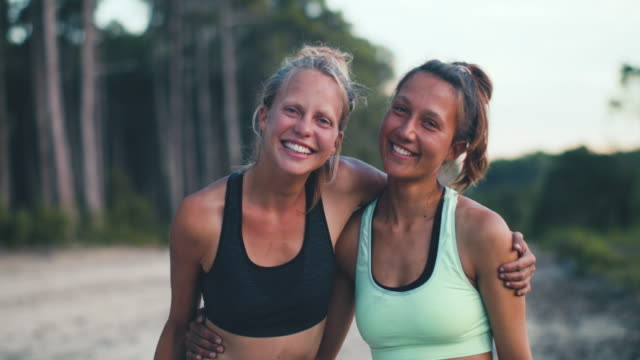 portrait of two beautiful young woman looking into camera after practicing yoga in the sand in the forest in the south of france. - arm around stock videos and b-roll footage