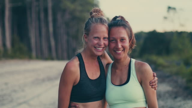 vídeos de stock, filmes e b-roll de portrait of two beautiful young woman looking into camera after practicing yoga in the sand in the forest in the south of france. - sutiã para esportes