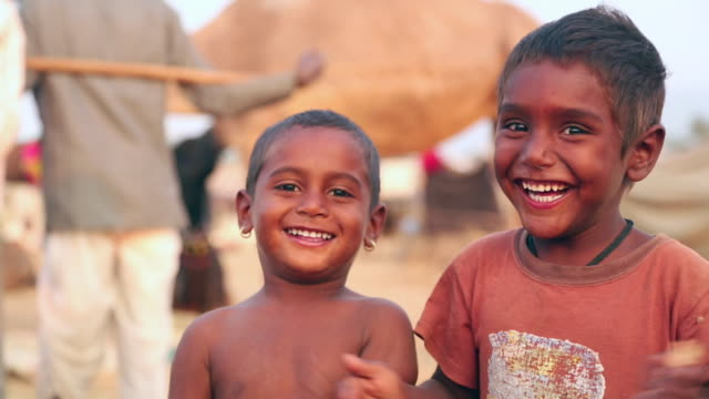 portrait of two boys clapping, rajasthan, india - povertà video stock e b–roll