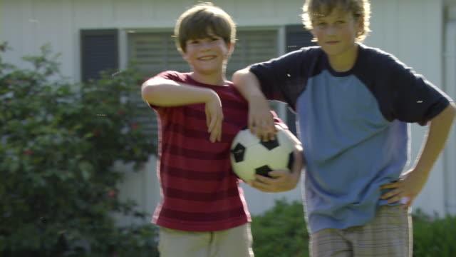 vídeos de stock, filmes e b-roll de ms shaky portrait of two boys (10-11) standing with soccer ball on lawn, encino, california, usa - amizade masculina