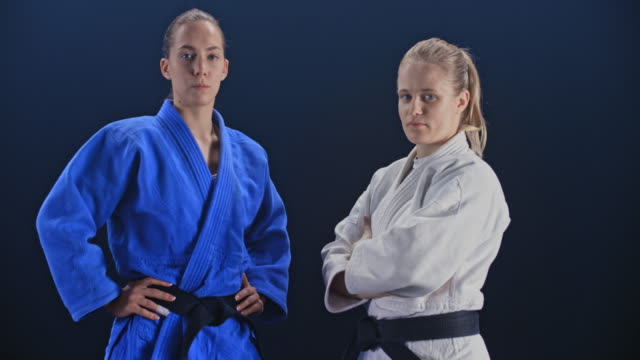 slo mo ds portrait of two female judoists on black background - world sports championship stock videos & royalty-free footage