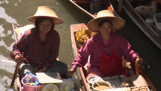 ms ha portrait of two fruit sellers on boat on damnoen saduak floating market, bangkok, thailand - thai ethnicity stock videos & royalty-free footage