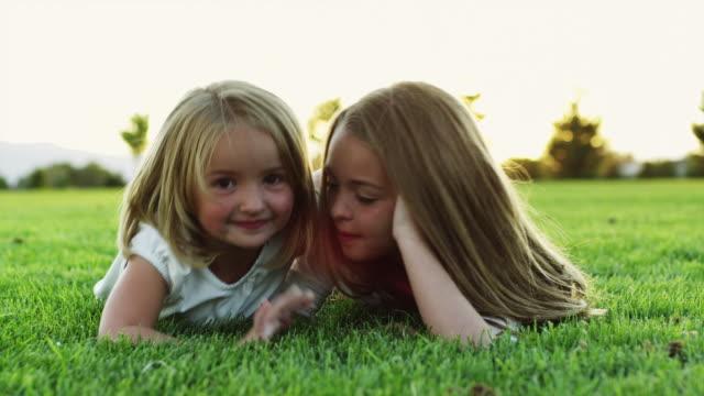stockvideo's en b-roll-footage met ms slo mo portrait of two girls (4-11) lying on grass in park / orem, utah, usa - orem utah