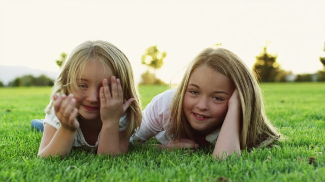 ms portrait of two girls (4-11) lying on grass in park / orem, utah, usa - gras stock-videos und b-roll-filmmaterial