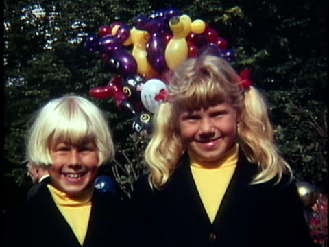 vídeos de stock e filmes b-roll de 1970 cu portrait of two girls (6-7, 8-9) wearing matching outfits with bunch of balloons in background, denmark - 1970