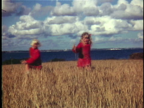 vidéos et rushes de 1970 ws cu portrait of two girls (6-7, 8-9) wearing matching red outfits running through grassy field, denmark - 1970