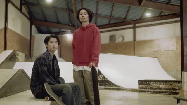 ritratto di due skateboarder maschi giapponesi nello skate park (slow motion) - fashion show video stock e b–roll