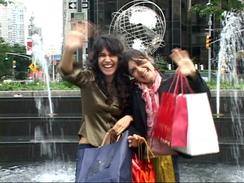 vidéos et rushes de ms, portrait of two laughing women with shopping bags in columbus circle, new york city, new york, usa - cadrage aux genoux