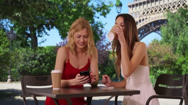 vidéos et rushes de portrait of two lovely women looking at phone in dresses near eiffel tower - personnes belles