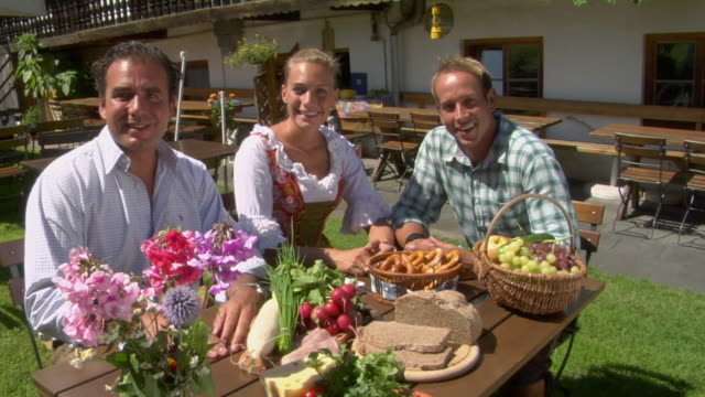 stockvideo's en b-roll-footage met ms portrait of two men and woman in dirndl dress at lunch table, bavaria, germany - vrouw met een groep mannen